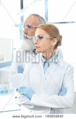 Two Scientists In White Coats And Goggles Looking Away And Posing In Chemical Laboratory