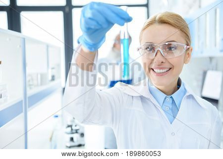 Smiling Chemist In Protective Eyeglasses Holding Test Tube With Reagent In Lab