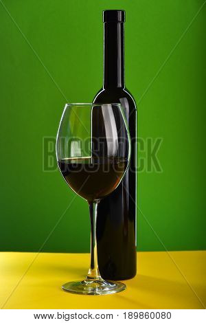Glass Filled With Red Wine Near Dark Bottle