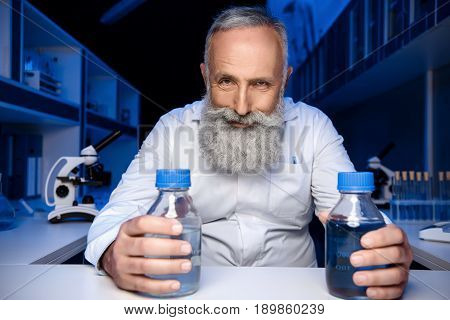 Portrait Of Cunning Scientist Holding Bottles With Reagents And Looking At Camera In Laboratory