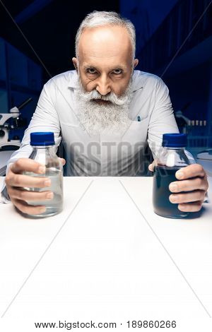 Portrait Of Evil Scientist With Bottles With Reagents Looking At Camera At Workplace
