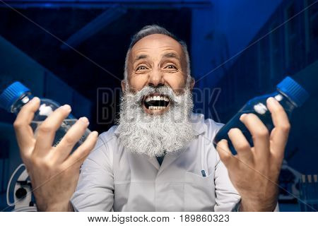 Portrait Of Excited Scientist Holding Bottles With Reagents In Laboratory