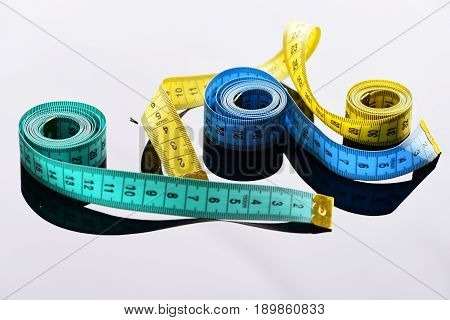 Rolls Of Cyan, Yellow And Blue Measuring Tapes With Reflections