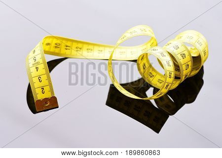 Roll of yellow tape for measuring untwisted curly on light grey surface with reflection