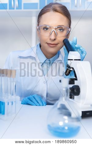 Portrait Of Smiling Scientist Using Microscope While Working With Reagents In Lab
