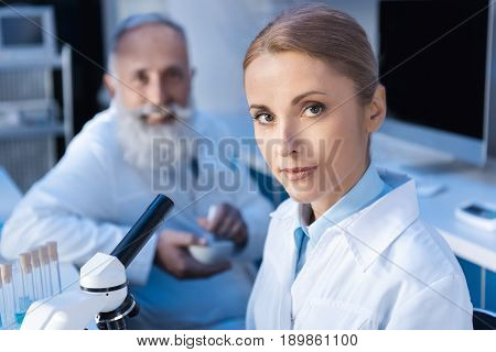 Two Scientists In Lab Coats Looking At Camera While Working At Laboratory