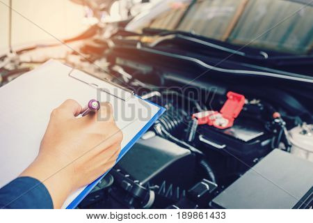 Mechanic Holding A Clipboard Of Service Order Working In Garage. Repair Service.