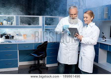 Smiling Laboratory Technicians In Lab Coats Looking At Digital Tablet During Work In Laboratory