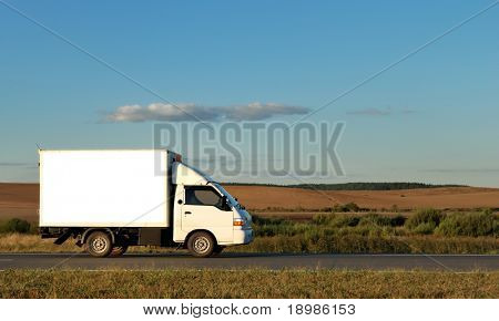 White Light-duty truck on highway over blue sky. See my portfolio for trucks and lorries