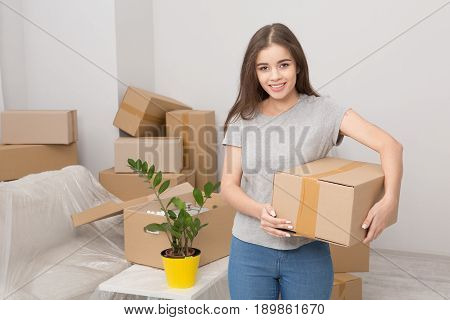 Young female standing with in the room full of boxes. Woman after relocating in the living room holding box ready to unpack things.