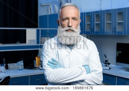 Serious Grey Haired Scientist In Lab Coat Looking At Camera With Arms Crossed
