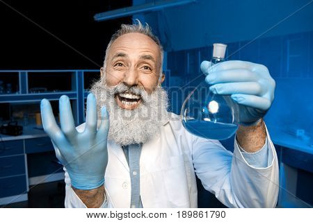 Happy Grey Haired Scientist Celebrating Success Of Scientific Experiment And Holding Flask With Reag