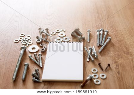 Construction tools. The screws, nuts and bolts arranged around blank spiral bound note book paper on wooden background. Repair, home improvement concept. Free space for text, top view, flat lay