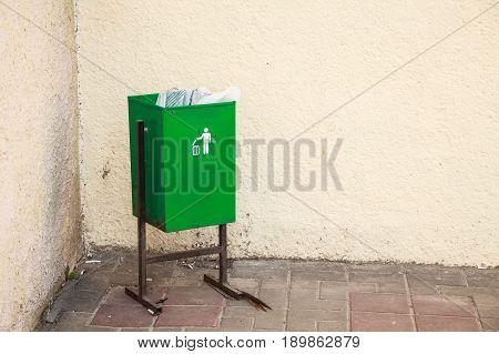 Close up green metal public garbage bin standing in the corner