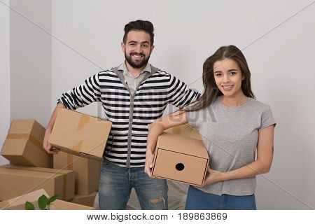 Attractive young couple is moving, smiling and holding boxes while standing among unpacked boxes. Happy man and woman relocating to new apartment unpacking things.
