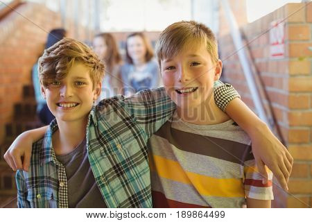 Portrait of smiling schoolboys standing with arm around in corridor at school
