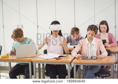 School girl sitting in classroom using virtual reality headset at school