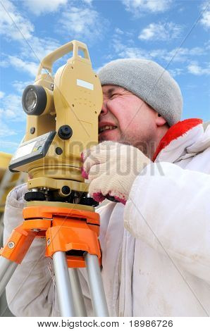 Land surveyor working with theodolite equipment at a construction site in winter over blue sky poster