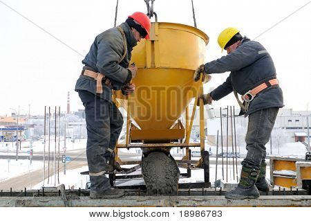 construction building workers at construction site pouring concrete in form
