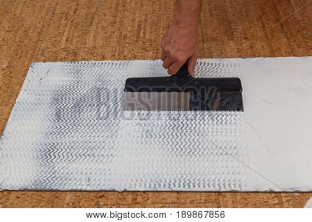 isolating panels for the economy of heat building materials for repair of houses and apartmentsimposition of glue a spatula on an isolating panel