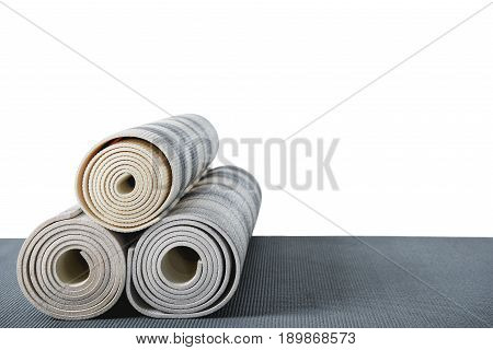 Yoga Mats Lying On Grey Mat Isolated On White With Copy Space