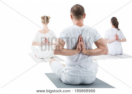 Back view of sporty young people sitting in lotus position with namaste mudra sign