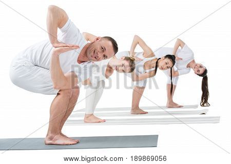 Young Women With Trainer Practicing Revolved Chair Yoga Pose On Mats