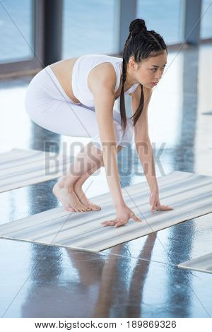 side view of asian woman practicing crane pose on yoga pose