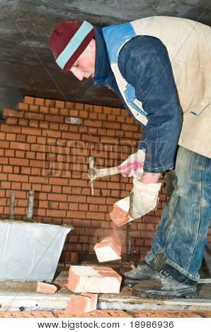 construction mason worker bricklayer during a brickwork with hack