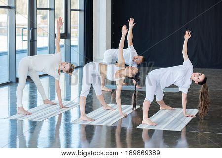 Girls Doing Half Moon Pose (ardha Chandrasana) With Instructor Indoors
