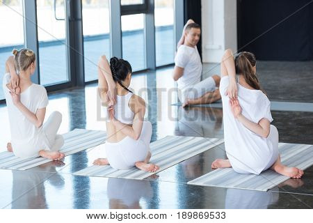 Women And Trainer Performing Gomukhasana Or Cow Face Pose On Yoga Mats