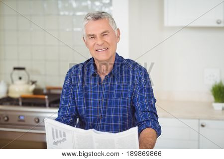Portrait of senor man reading newspaper in kitchen at home