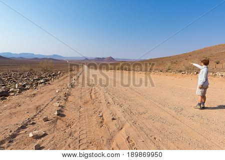 Tourist Walking On 4X4 Road Crossing The Colorful Desert At Twyfelfontein, In The Majestic Damaralan