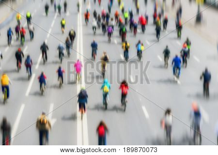 Abstract blurred background of Large group of bicyclists on street, city marathon. Participants and athletes go back to us, unrecognizable. Concept of Sport, fitness, healthy lifestyle. For backdrop with blur. Selective focus