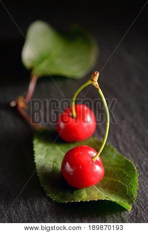 cherries with leaf on black ardesia plate