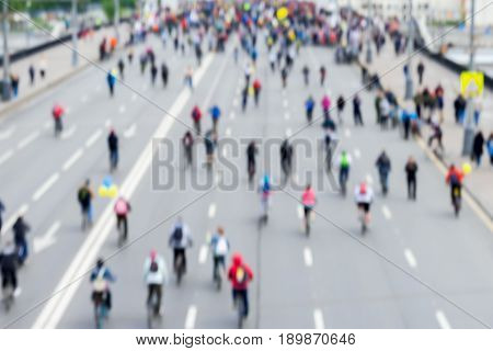 Abstract blurred background of mass cycling marathon in the streets of the city. Participants and athletes go back to us. Concept of Sport, healthy lifestyle, aktivity. Selective focus. For backdrop