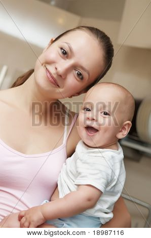 Happy mother holding the laughing child in her hands