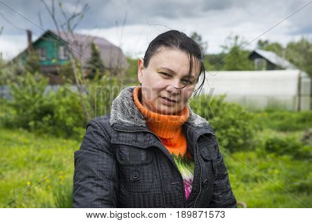 Portrait of a mature woman in the background of a village house