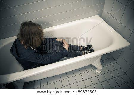 Stressed Teenage Girl Sitting In Empty Bath