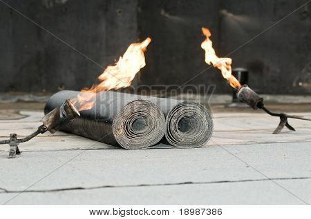 roofing felt roll and two torch blowpipes with open flame