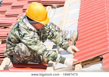 builder roofer working with red clay tile at roofing construction works