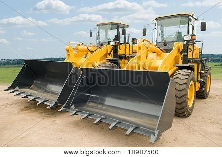 Two Loaders excavators construction machinery equipment outdoors