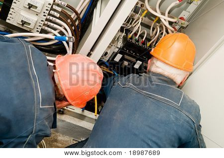 Two electrician man operating personnel installing and mounting new industrial wiring at voltage panel