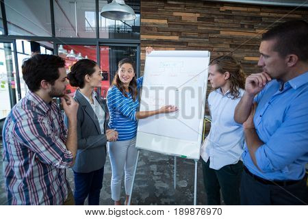 Team of businesspeople having discussion over flip chart in office