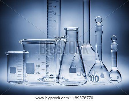 Different laboratory beakers and glassware in blue