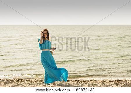 Young beautiful woman on the beach in azure long dress with mobile phone in hand. Selective focus.