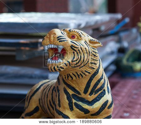 Thailand, Kanchanaburi. 23 Feb 2010: a sculpture of a Tiger with coins in the mouth - the symbol of the Tiger temple, Kanchanaburi, Thailand