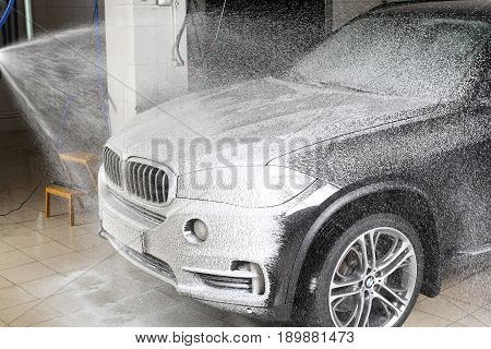 MOSCOW RUSSIA - OCTOBER 4 2015: The worker washing of the car under a high pressure. Car service.