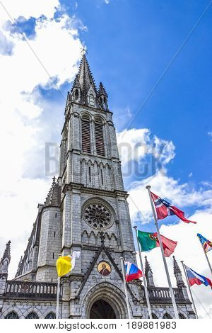 Basilica of our Lady of the Rosary and flags of different countries against the blue sky. Lourdes, France, Hautes Pyrenees