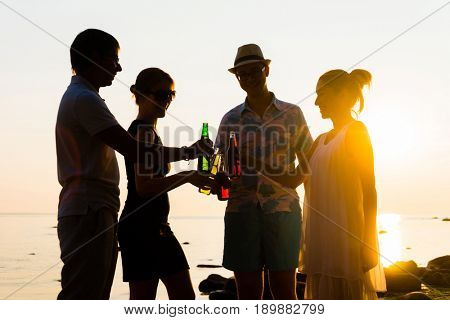 Happy friends drinking alcoholic drinks and having a party on a beach in the sunset. Man in hat enjoying a sunset on a beach and drinking a beer. Young, adult, freedom, beach, summer, concept.